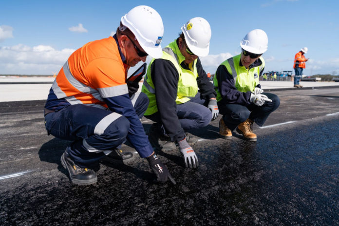 Workers inspecting the new layer of runway pavement